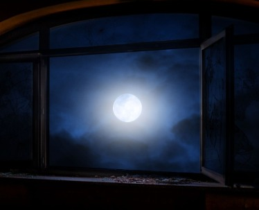 full moon through a window on a cloudy night